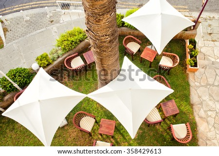 Outdoor chair with umbrella in the terrace. Cafe in Cyprus, Limassol. Top view, horizontal color image - stock photo