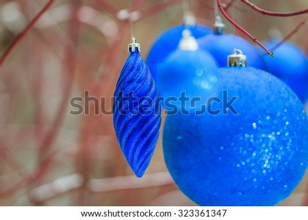 Outdoor Christmas decorations with textured sparkling blue bauble ornaments hanging on tree red branches - stock photo