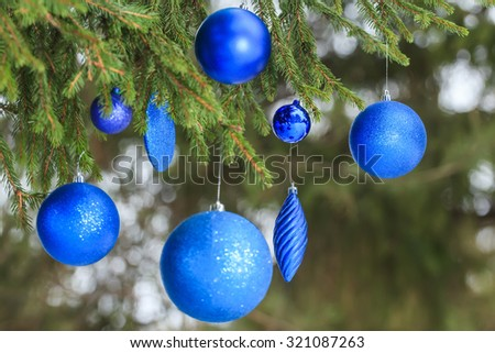 Outdoor Christmas navy blue glitter bauble ornaments are hanging on snowy spruce twig - stock photo