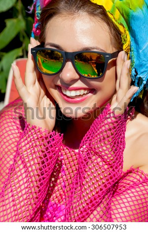Outdoor close up fashion portrait of young sexy smiling woman with perfect bronze tanned skin with pink lips and white teeth in bright pink beach dress and mirrored glasses.Holiday party.Luxury  - stock photo