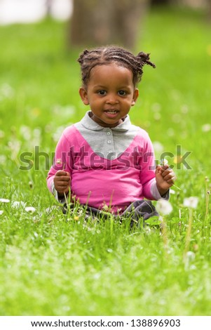 Outdoor close up portrait of a cute little young black girl smiling - African people - stock photo