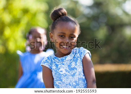Outdoor close up portrait of a cute young black girl smiling - African people - stock photo