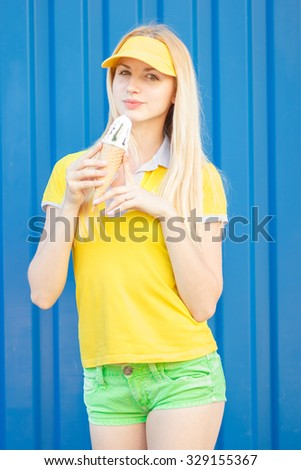 Outdoor closeup colorful portrait of young pretty blonde woman eating ice cream. Soft focus - stock photo