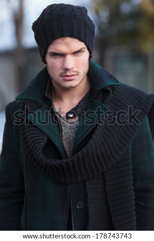 outdoor closeup portrait of a young fashion man looking into the camera - stock photo