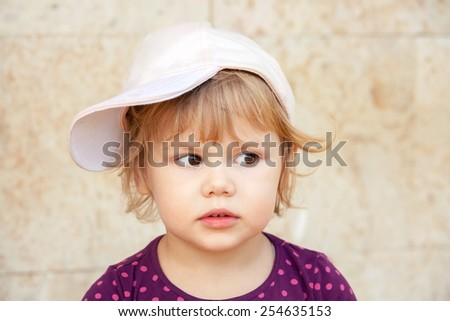 Outdoor closeup portrait of curious cute Caucasian blond baby girl in baseball cap - stock photo