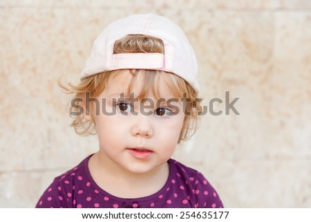 Outdoor closeup portrait of curious cute Caucasian blond baby girl in white baseball cap - stock photo