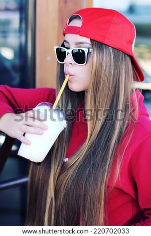 Outdoor closeup portrait of pretty stylish fashion girl having fun drinking chocolate milkshake in a cafe outdoors.  Lifestyle swag style photo - stock photo