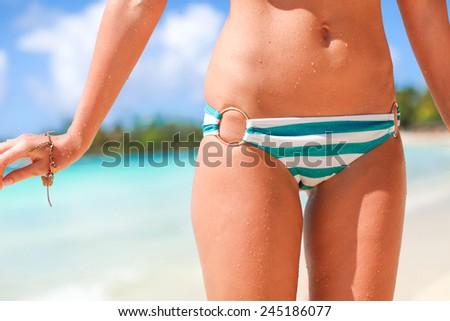 Outdoor closeup shot of young woman in stripe bikini sunbathing at white beach - stock photo