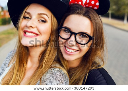 Outdoor  cute portrait of pretty girls best friends having fun together, smiling , emotions ,  cool spring outfit, bright colors, white teeth.   - stock photo