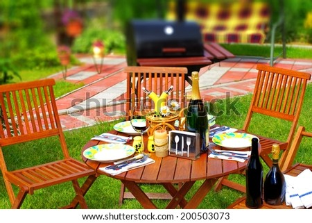 Outdoor Dining Scene in Backyard. BBQ Grill in background. Tilt-shift effect. - stock photo