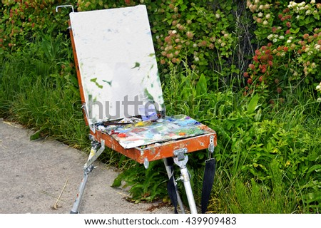 Outdoor easel with paints and paint a picture mounted on the park alley - stock photo
