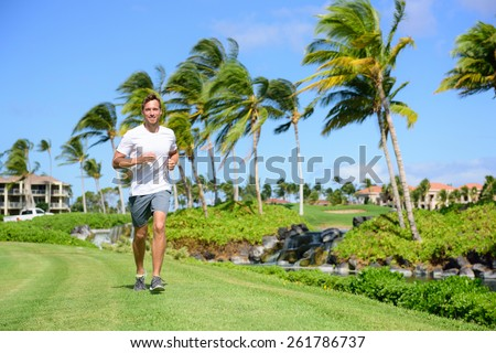 Outdoor exercise man running on grass in city park, resort area or upscale community. Happy young male runner staying fit exercising and living a healthy lifestyle training outside in summer nature. - stock photo