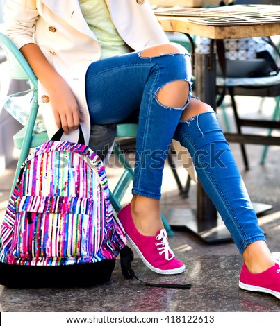 Outdoor fashion details, woman posing at city cafe, wearing vintage denim, bright shoes and backpack and classic coat, sunny bright colors, street style fashion. - stock photo