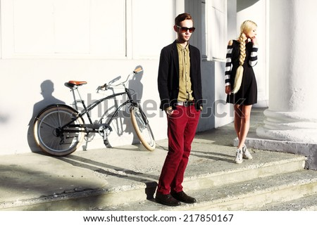 Outdoor fashion dressed hipster style couple posing in the city with vintage bicycle - stock photo