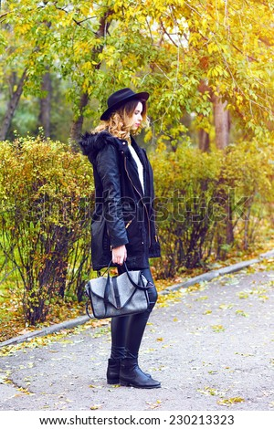 Outdoor fashion image of pretty woman walking at parka coat in nice fall autumn day, wearing trendy street style look, leather pants, parka, vintage hat boots and shoulder bag. - stock photo