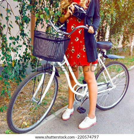 Outdoor fashion image of woman riding vintage hipster white bicycle, holding retro camera, wearing nice floral dress and warm cardigan, having mica day at city park. - stock photo