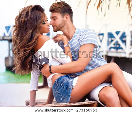 Outdoor Fashion lifestyle portrait of young perfect couple lay and relaxed on their vacation,wearing sunglasses and vintage clothes,bright sunny hipster couple hugs on the beach,warm colors.lovers - stock photo