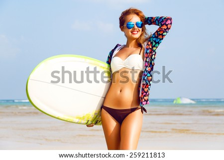 Outdoor fashion lifestyle summer portrait of stunning sexy surfer woman, wearing bright outfit makeup and sunglasses. Posing near clear blue ocean, enjoy her vacation. - stock photo