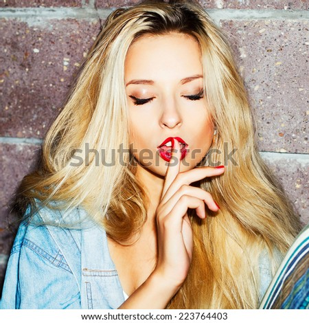 Outdoor fashion night flash portrait of sexy pretty sensual blonde woman with finger close to her lips and closed eyes showing silence gesture  - stock photo