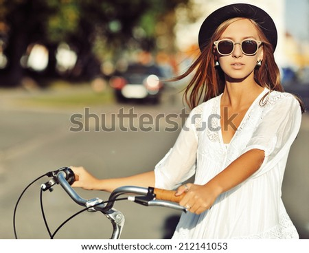 Outdoor fashion portrait of a beautiful blonde with bike  - stock photo