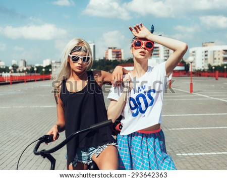 Outdoor fashion portrait of attractive young women with bicycle and roller skates. Two teen swag girls - stock photo