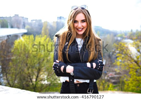 Outdoor fashion portrait of cute blonde woman smiling and having fun, urban city background, long hairs, bright make up, biker leather jacket, street fashion. - stock photo