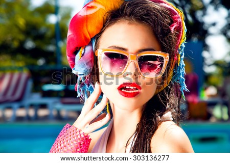 Outdoor fashion portrait of glamour lady enjoying her holidays,Summer sunny portrait of funny hipster girl having fun near pool on exotic tropical island cute outfit,ponytails hairstyle,wet hair,nail - stock photo