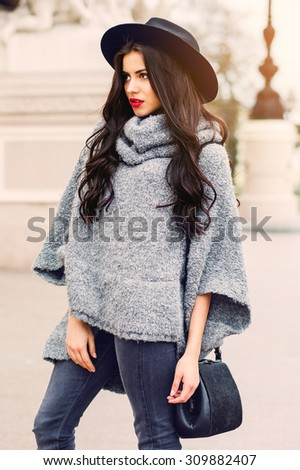 Outdoor fashion portrait of glamour sensual young stylish lady wearing trendy fall outfit , black hat , grey sweater and leather bag. Cold season.Red lips. Warm  clothes. - stock photo