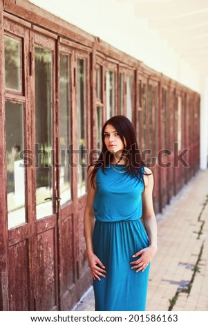 Outdoor fashion portrait of pretty sensual sexy girl posing in corridor wit lot of red old vintage doors in summer - stock photo