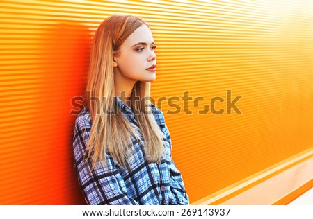 Outdoor fashion portrait of pretty woman in the city against the colorful orange wall - stock photo
