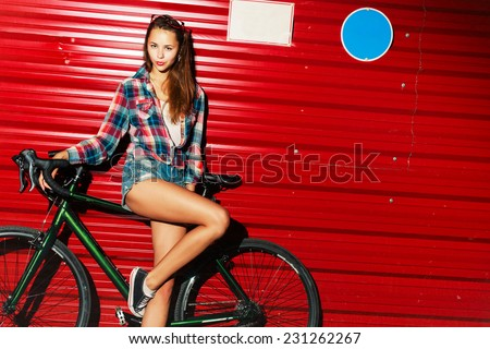Outdoor fashion portrait of pretty young girl posing with sport bicycle on red background and have fun lifestyle mood  - stock photo