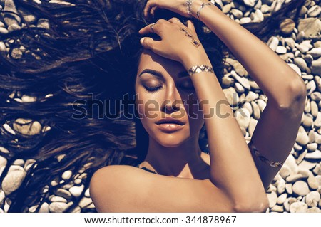Outdoor fashion portrait of sexy lady lying at beach - stock photo