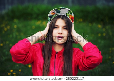 Outdoor fashion portrait of stylish girl. Young brunette woman posing, wearing swag floral cap. Lifestyle portrait bright toned colors. - stock photo