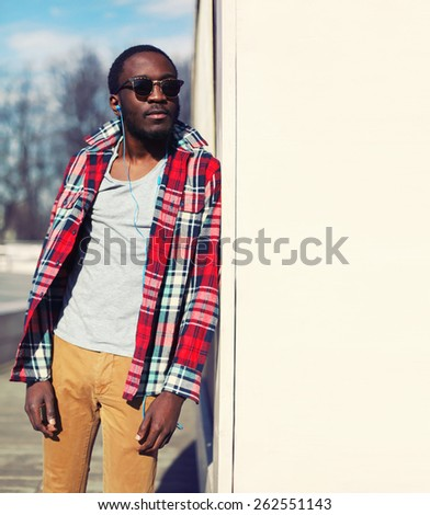 Outdoor fashion portrait of stylish young african man listens to music and enjoys freedom, wearing a plaid hipster red shirt and sunglasses, posing near urban white wall for background, copy space - stock photo