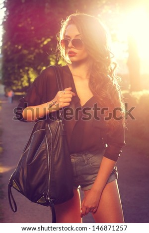 outdoor fashion portrait of young beautiful stylish girl posing at summer sunset - stock photo