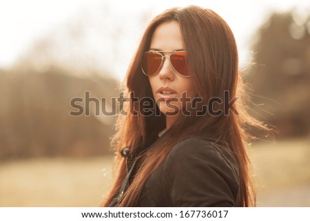 Outdoor fashion portrait of young brunette woman in sunglasses - stock photo