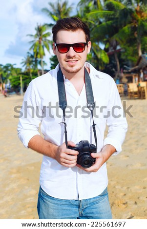 Outdoor fashion portrait of young handsome man photographer with camera posing on the tropic island beach smiling and having fun in summer  - stock photo