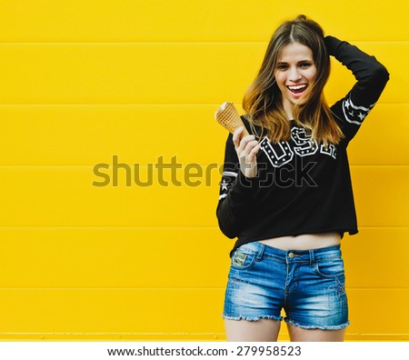 Outdoor fashion portrait of young hipster girl with  ice-cream on yellow wall background  - stock photo