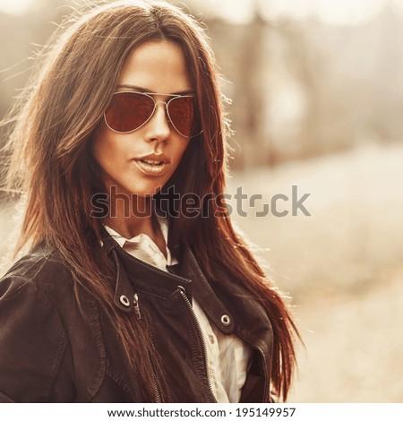 Outdoor fashion portrait of young pretty woman in sunglasses - stock photo
