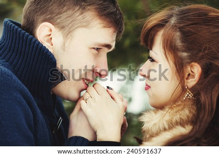 outdoor fashion portrait of young sensual couple in cold winter wather. love and kiss - stock photo