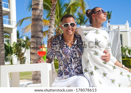 Outdoor fashion portrait of young sensual couple in vacation. Attractive elegant young couple drinking a cocktail. - stock photo