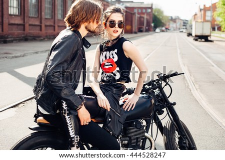 outdoor fashion portrait of young sensual couple sitting on vintage motorcycle - stock photo