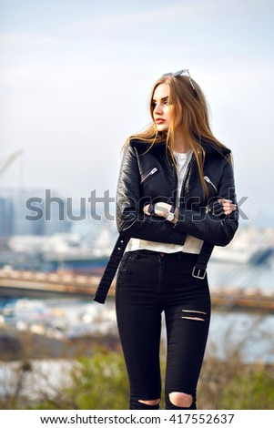Outdoor fashion portrait of young stunning woman posing at city port, grunge urban style, vintage denim, leather jacket and gloves, trendy outfit. Sad thinking mood. - stock photo