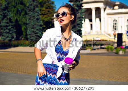 Outdoor fashion portrait of young stylish hipster elegant girl, walking alone at sunny day, at European city center, wearing romper, jacket and sunglasses, joy, vacation, travel, bright colors. - stock photo