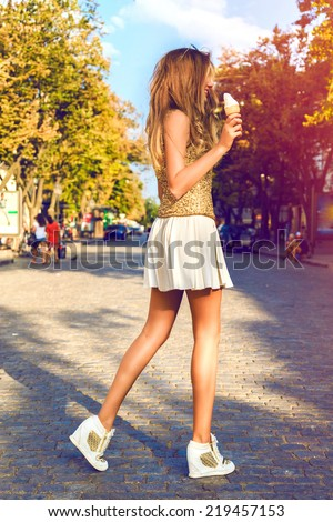 Outdoor fashion portrait of young trendy woman with perfect long legs at elegant cute outfit, walking alone at city center and eating tasty vanilla cone ice-cream, Bright vintage Instagram colors. - stock photo