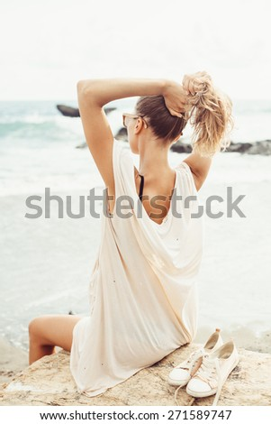 Outdoor fashion portrait summer beach style of Young happy girl in sunglasses near the sea and looking on the water and waiting for somebody in ocean - stock photo