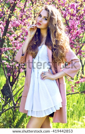 Outdoor fashion spring portrait of sunning sensual blonde woman, posing at amazing blossom garden. Wearing pink jacket and feminine dress, elegant glamour style. - stock photo
