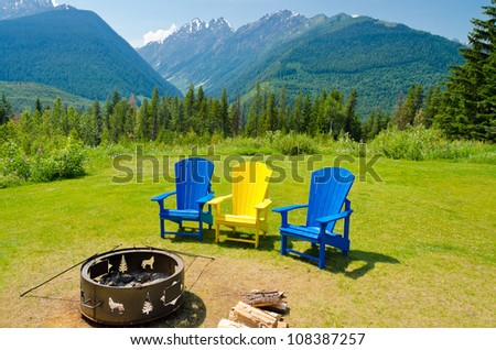 outdoor fireplace with three colorful chairs over fantastic mountain view - stock photo