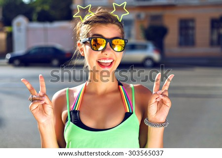 Outdoor funny lifestyle portrait of young pretty happy girl having fun on the street, showing piece science, laughing, bright hipster neon outfit, positive, joy, travel, vacation. - stock photo