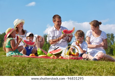 outdoor group portrait of happy family having picnic on green grass in park and enjoying watermelon - stock photo